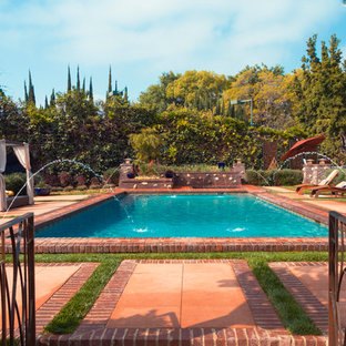 Large country backyard rectangular lap pool in Los Angeles with brick pavers and a water feature.