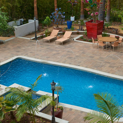 Hot tub - large tropical backyard brick and rectangular lap hot tub idea in Los Angeles