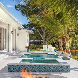 Foto de piscinas y jacuzzis actuales, rectangulares, en patio trasero, con adoquines de hormigón