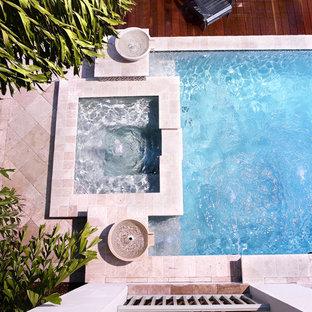 Ejemplo de piscinas y jacuzzis alargados, tropicales, de tamaño medio, rectangulares, en patio trasero, con adoquines de piedra natural