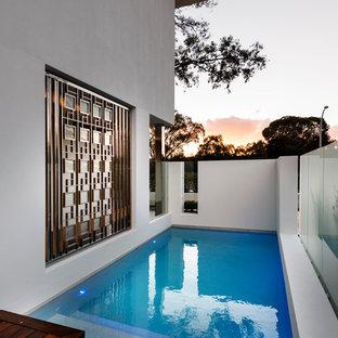 """Foto di una piscina contemporanea a """"L"""" nel cortile laterale con pedane"""