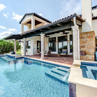 This is an example of a large country backyard rectangular infinity pool in Austin with tile.