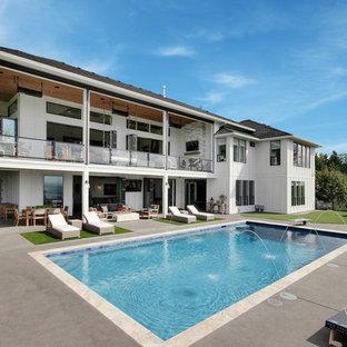 Ejemplo de piscina con fuente alargada, de estilo de casa de campo, grande, rectangular, en patio trasero, con suelo de hormigón estampado