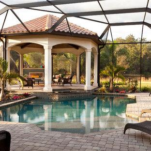 Modelo de piscina mediterránea, extra grande, en patio trasero, con adoquines de ladrillo