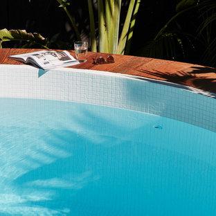 Diseño de piscina elevada, actual, de tamaño medio, redondeada, en patio trasero, con adoquines de piedra natural