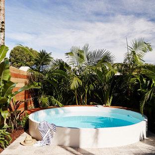 Diseño de piscina elevada, contemporánea, de tamaño medio, redondeada, en patio trasero, con adoquines de piedra natural