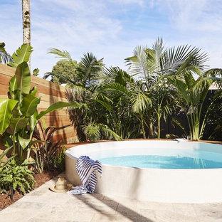 Esempio di una piscina fuori terra stile marinaro rotonda dietro casa con pavimentazioni in pietra naturale
