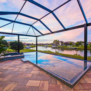 This is an example of a large country backyard l-shaped infinity pool in Tampa with a water feature and concrete pavers.