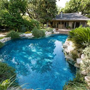 Ejemplo de piscinas y jacuzzis naturales, rústicos, de tamaño medio, a medida, en patio trasero, con adoquines de ladrillo