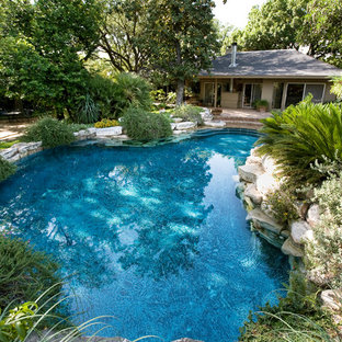 Inspiration for a mid-sized country backyard custom-shaped natural pool in Austin with brick pavers and a hot tub.