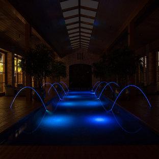 Imagen de piscina con fuente clásica, grande, rectangular y interior, con adoquines de ladrillo