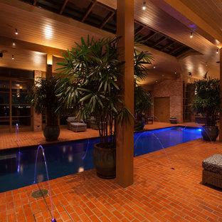 Foto di una grande piscina coperta classica rettangolare con fontane e pavimentazioni in mattoni
