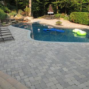 Modelo de piscinas y jacuzzis naturales, clásicos renovados, de tamaño medio, a medida, en patio trasero, con adoquines de piedra natural