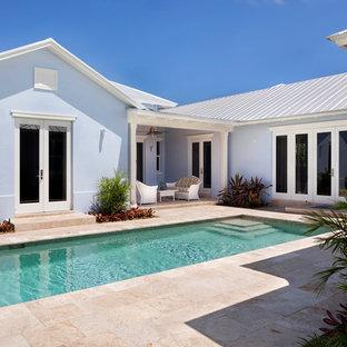 Diseño de piscina alargada, costera, extra grande, rectangular, en patio trasero, con adoquines de piedra natural