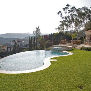 """Immagine di una grande piscina a sfioro infinito mediterranea a """"C"""" dietro casa con piastrelle"""