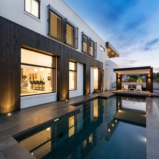 Inspiration for a large contemporary backyard custom-shaped pool in Melbourne with concrete pavers.