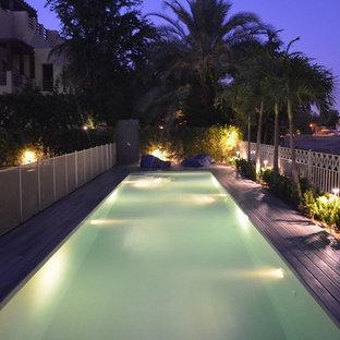 Ejemplo de piscina alargada, escandinava, de tamaño medio, rectangular, en patio trasero, con entablado