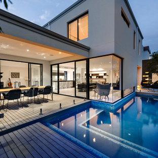 Diseño de piscina contemporánea, en forma de L, en patio trasero, con entablado