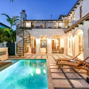 Immagine di una grande piscina mediterranea personalizzata nel cortile laterale con piastrelle