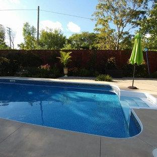 Modelo de piscina tradicional, de tamaño medio, rectangular, en patio trasero, con losas de hormigón