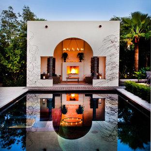 Modelo de casa de la piscina y piscina mediterránea, grande, rectangular, en patio trasero, con adoquines de hormigón