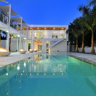 Diseño de piscina alargada, minimalista, de tamaño medio, rectangular, en patio, con adoquines de hormigón