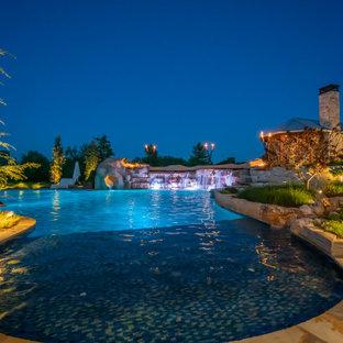Ejemplo de piscina natural, de estilo de casa de campo, extra grande, a medida, en patio trasero, con privacidad y adoquines de piedra natural