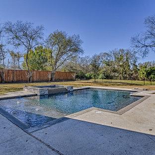 Modelo de piscinas y jacuzzis alargados, de estilo americano, grandes, rectangulares, en patio trasero, con losas de hormigón