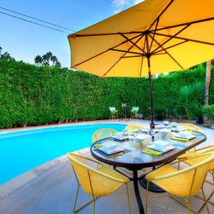 Ejemplo de piscina natural, vintage, grande, tipo riñón, en patio trasero, con losas de hormigón