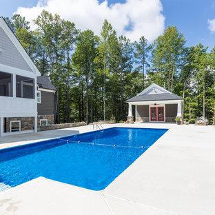 Ejemplo de casa de la piscina y piscina alargada, de estilo americano, grande, rectangular, en patio trasero, con losas de hormigón