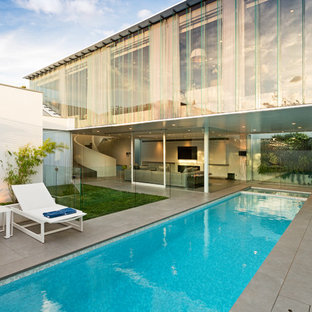 Large contemporary backyard rectangular pool in Melbourne with tile.