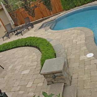 Diseño de casa de la piscina y piscina alargada, tradicional renovada, de tamaño medio, tipo riñón, en patio trasero, con adoquines de hormigón