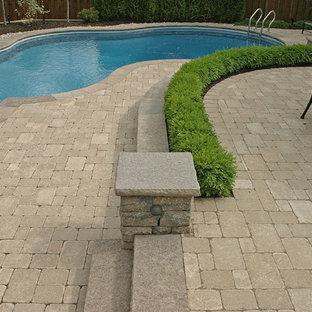 Ejemplo de casa de la piscina y piscina alargada, tradicional renovada, de tamaño medio, tipo riñón, en patio trasero, con adoquines de hormigón