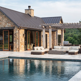 This is an example of a large country backyard rectangular lap pool in DC Metro with a pool house and natural stone pavers.