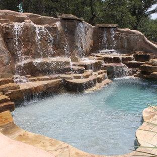 Ispirazione per una grande piscina naturale design personalizzata dietro casa con un acquascivolo e pedane