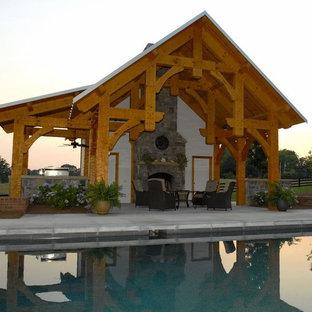 Esempio di una grande piscina naturale stile rurale rettangolare dietro casa con una dépendance a bordo piscina e lastre di cemento
