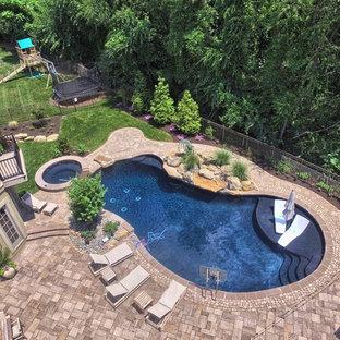 Modelo de piscinas y jacuzzis contemporáneos, grandes, tipo riñón, en patio trasero, con adoquines de hormigón