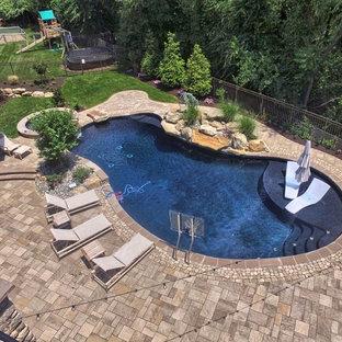 Ejemplo de piscinas y jacuzzis contemporáneos, grandes, tipo riñón, en patio trasero, con adoquines de hormigón