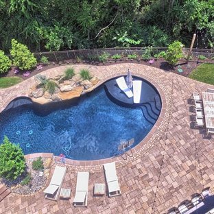 Large contemporary backyard kidney-shaped pool in Philadelphia with a hot tub and concrete pavers.