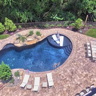 """Ispirazione per una grande piscina design a """"C"""" dietro casa con una vasca idromassaggio e pavimentazioni in cemento"""