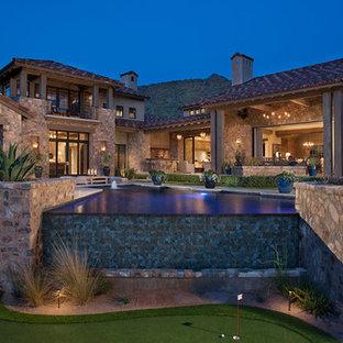 Imagen de piscina con fuente infinita, de estilo americano, grande, a medida, en patio trasero