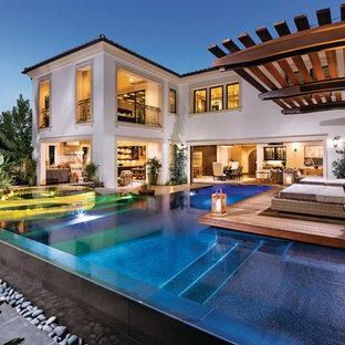 Diseño de piscinas y jacuzzis tradicionales renovados, en forma de L, en patio trasero, con entablado