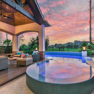 Exemple d'une grand piscine naturelle et arrière chic rectangle avec un bain bouillonnant et une dalle de béton.
