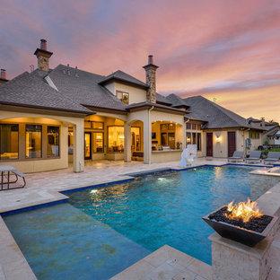 Esempio di una grande piscina naturale chic rettangolare dietro casa con una vasca idromassaggio e pavimentazioni in pietra naturale