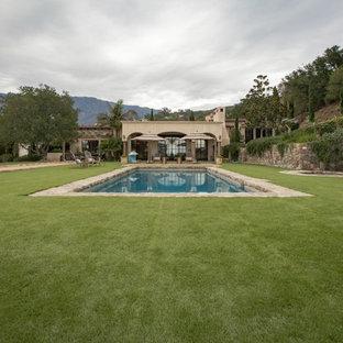 Großer Mediterraner Pool hinter dem Haus in rechteckiger Form mit Natursteinplatten in Santa Barbara