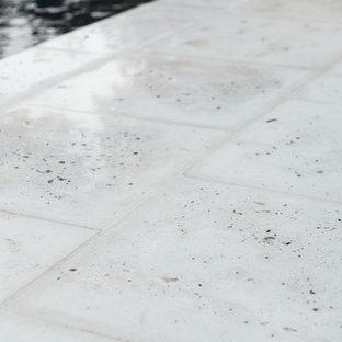 Foto de casa de la piscina y piscina alargada, tropical, rectangular, en patio trasero, con adoquines de hormigón