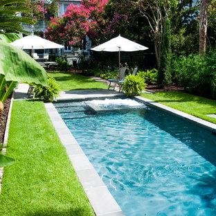 Foto di una grande piscina monocorsia tradizionale rettangolare dietro casa con pavimentazioni in cemento