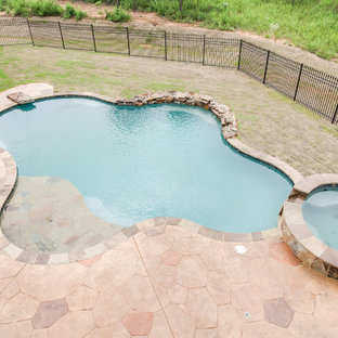 Idee per una grande piscina classica personalizzata dietro casa con una vasca idromassaggio e pavimentazioni in pietra naturale