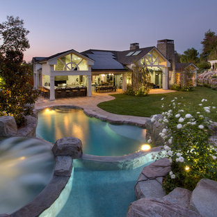 Hot tub - large traditional backyard stone and custom-shaped hot tub idea in Orange County