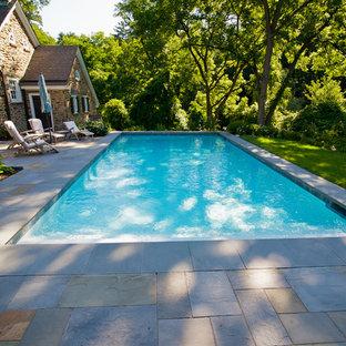 Diseño de piscina clásica, de tamaño medio, rectangular, en patio lateral, con adoquines de piedra natural